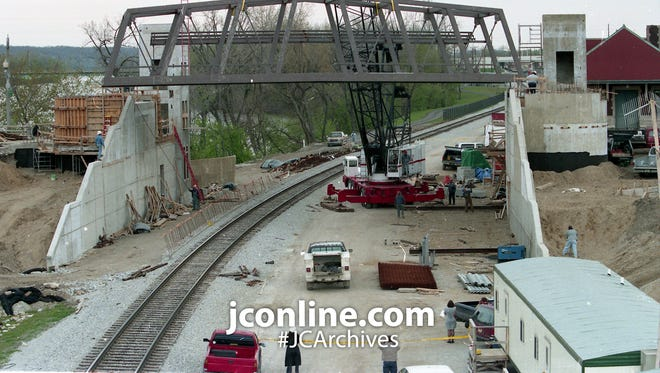 A pedestrian bridge now crosses the railroad tracks along the Wabash River in Lafayette. Walsh Construction workers used a crane to put the pre-assembled bridge into place. Photo taken April 27, 1995.
