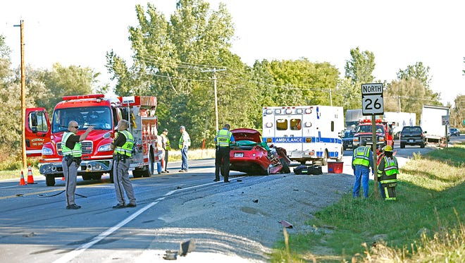 Emergency personnel work the scene of a fatal crash between a Dodge Stratus and a semi, at the intersection of County TC and State Highway 26 Tuesday, Sept. 22.