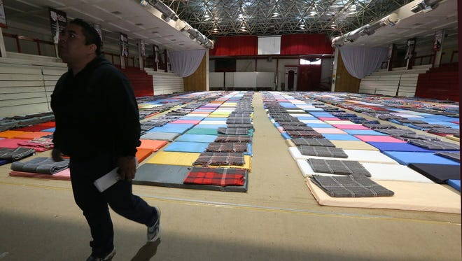 Ricardo Zuñiga, cultural affairs coordinator for the Instituto Tecnológico de Ciudad Juárez, walks past 500 mats and blankets students put down at the university's gymnasium floor Tuesday afternoon. The school was preparing for out-of-town visitors who do not have a hotel room or another place to stay the night for Wednesday's visit by Pope Francis to this border city of 1.5 million people.