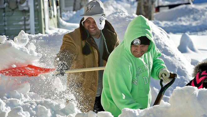 Jose Sanchez, left, and Irwin Perez are in good spirits as they shovel snow Sunday, Jan. 24, 2016, in Chambersburg, Pa. Winter Storm Jonas dropped a few feet of snow on the area.