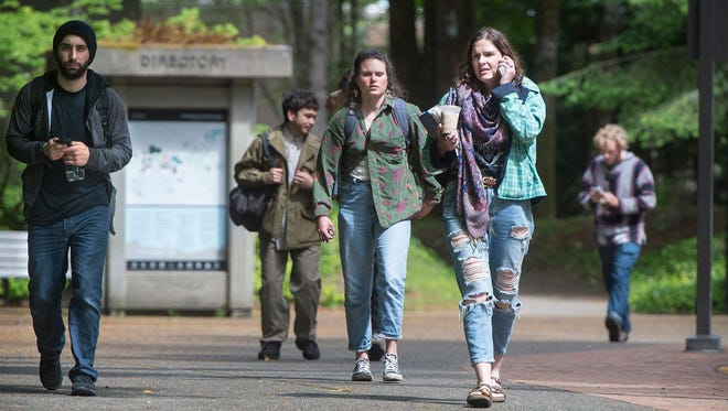 In this June 1, 2017, file photo, students leave the Evergreen State College campus in Olympia, Wash., after a threat prompted a student alert and evacuation. A 53-year-old New Jersey man was arrested Monday, July 3, 2017, on charges of calling in threats to the college.