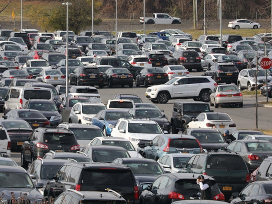 Vehicles look for a space in a crowded parking lot