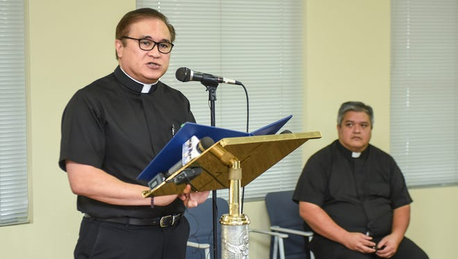 Monsignor James Benavente, standing, speaks at a press conference as Father Jeff San Nicolas looks on, on Friday, Sept. 30.