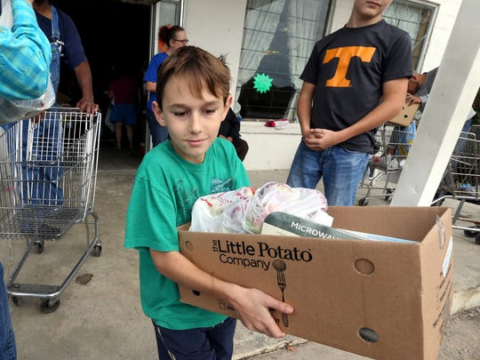 Alden DeGennaro loads up food boxes at the Midland Baptist Church Journey of Hope food bank.