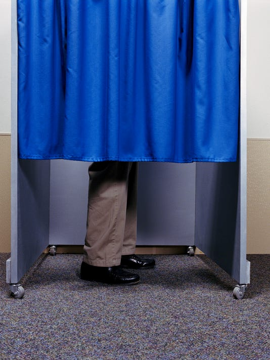 Man standing behind curtain in booth, low section