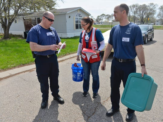 St. Cloud firefighters Dan Ford, left, and Jeff Gendreau check with American Red Cross Assistant Director of Preparedness Katie Ward to see where they are headed for their next smoke detector install Saturday at the Cloverleaf Mobile Home Community.