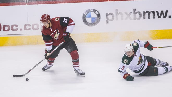 Coyotes' Michael Stone (26) jukes Wild's Charlie Coyle (3) before he passes in the third period at Gila River Arena in Glendale, AZ  on October 15, 2015.