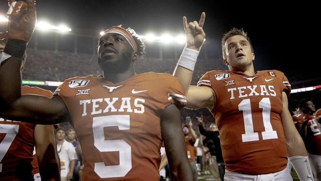 """Texas defensive back D'Shawn Jamison and quarterback Sam Ehlinger  hold up the """"Hook 'em Horns"""" sign for the playing of """"The Eyes of Texas"""" following Texas' 36-30 win over Oklahoma State last September."""
