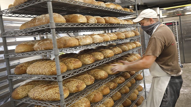 Owner Peter Nyberg inspects fresh bread just out of the oven at Hearth Artisan Bread in Plymouth. Greg Derr/ The Patriot Ledger