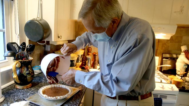 Tom Greene fills a pie shell with filling for his Chocolate Chess Pie at home in Shelby on Thursday.
