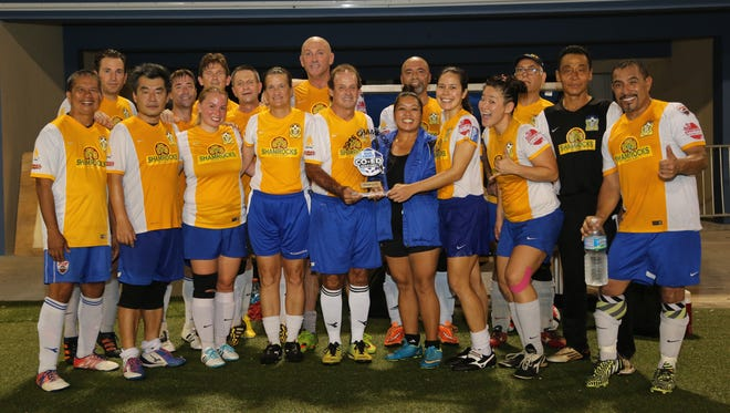 """The Rovers Masters pose with the 2016 Bud Light Co-Ed Masters Soccer League champions trophy during an awards ceremony Aug. 26 at the Guam Football Association National Training Center. Front row, from left: Jose Gallego, James Oh, Camarin Perez, Cheri Stewart, George Stewart, GFA Executive Committee Member Tina Esteves, Anjelica Perez, Gajee Anna Parsons, Michael Lee, and Julio Gonzales. Back row, from left: Matthew Larkin, Peter Houk, Craig Wade, Kieron """"Pip"""" Ward, Pedro Walls, Enrique Interian, and Manoucher Sabeti."""