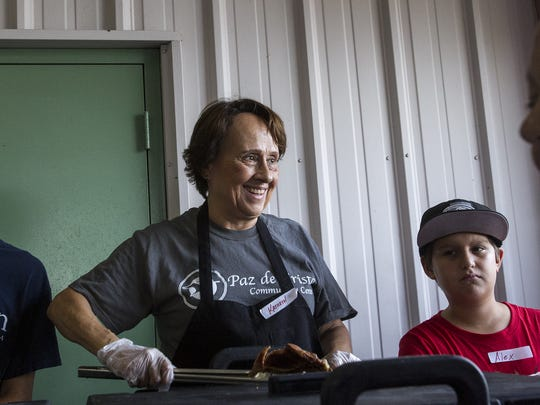 Kitchen staff Kathryn Samaniego, of Gilbert, serves guests at the dinner line at the Paz de Cristo Outreach Center in Mesa on July 19, 2016. The local organization serves dinner for the homeless daily through an initiative called Housing our Heroes.