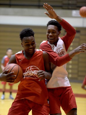 Richmond High School boys basketball player Rickie Wedlow, left, and Christian Harvey react after a dunk during practice Saturday, Nov. 12, 2016 in the Tiernan Center.