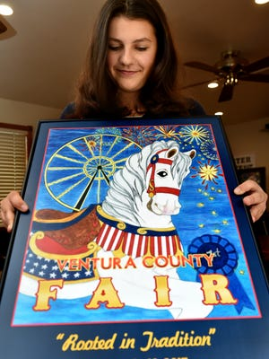 "Anna Sorensen, of Simi Valley, holds the unveiled poster for this year's Ventura County Fair after being named the winner of the 2017 poster contest. Sorensen depicted the theme, ""Rooted in Tradition,"" with an illustration of a white carousel horse framed by a Ferris wheel and fireworks in the distance."