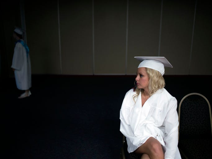 Natalie Smith relaxes in an air-conditioned room before commencement proceedings as Delmar High School graduates its class of 2014 at the Wicomico Youth & Civic Center in Salisbury.