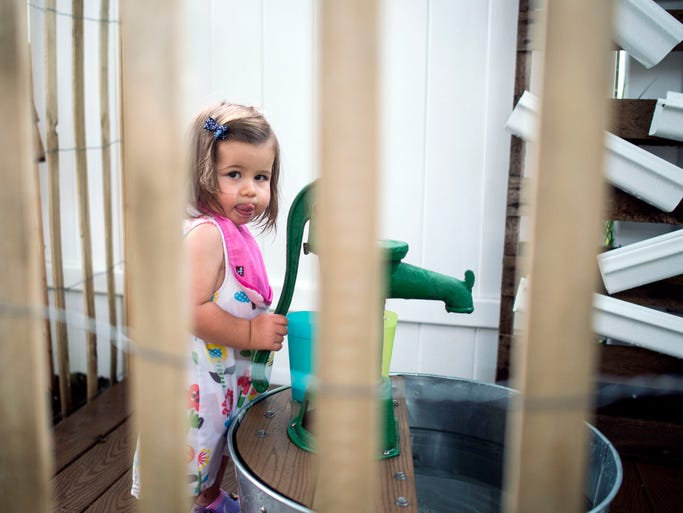 Scarlett Stazzone, 1, gathers cups of water for mud pies at Child's Play by the Bay in Lewes.