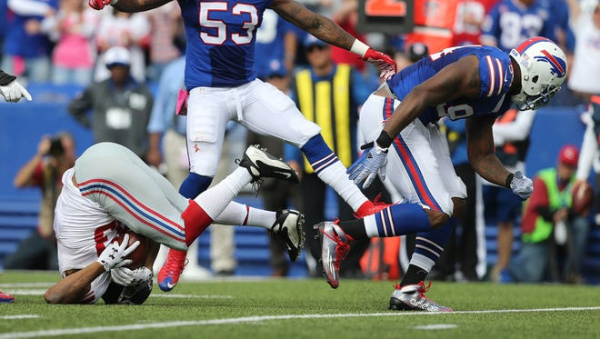 In this file photo, Giants RB Rashad Jennings is dumped on his head after being stuffed by Bills Mario Williams.