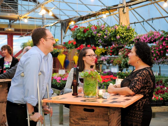 Guests enjoy drinks before dinner at Johnson's Farm greenhouses.