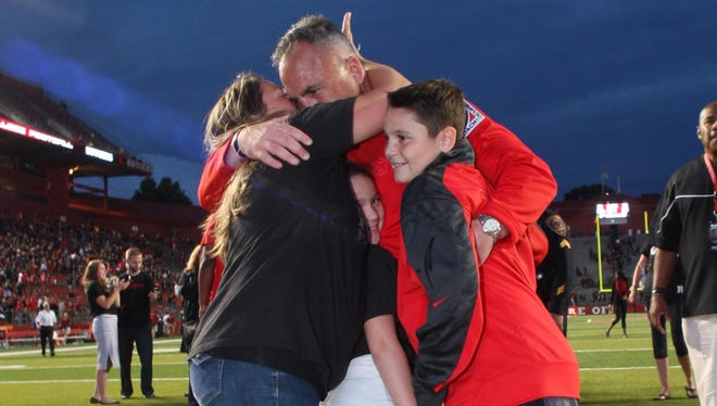 Rutgers coach Kyle Flood celebrates a comeback win against Arkansas with his family in September 2013.
