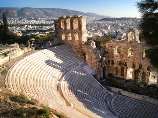 In this Dec. 11, 2016 photo, the Odeon of Herodes Atticus, or Herodeon, a stone theatre structure located on the southwest slope of the Acropolis of Athens, is seen against a backdrop of Athens. For travelers with more than beaches on their minds, there's plenty of upside to a brief winter visit to Athens that avoids the crowds and heat of summer.