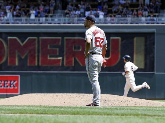 Boston Red Sox pitcher Eduardo Rodriguez, center, stands off the mound as the Minnesota Twins' Kurt Suzuki heads home on a three-run home run in the fourth inning Saturday in Minneapolis.