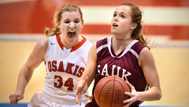 Jill Klaphake of Sauk Centre drives to the basket as Brittney Sadlemyer of Osakis tries to break her concentration during the first half of Tuesday's West Sub-Section 6-2A playoff game at St. John's University in Collegeville.