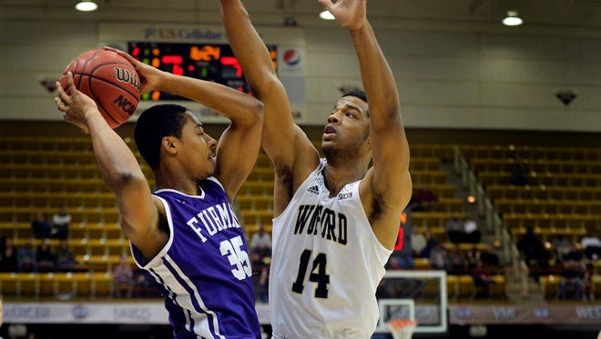 Furman guard Daniel Fowler (35) is pressured in the corner by Wofford guard Spencer Collins (14) during the 2015 Southern Conference Men's Basketball Tournament Championship at the U.S. Cellular Center in Asheville on Monday