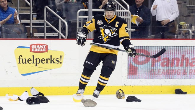 Pittsburgh Penguins center Sidney Crosby (87) looks at hats thrown on the ice after scoring a hat trick against the Florida Panthers.