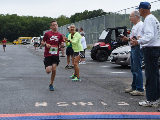 Brendan Meyer, 12, of LaGrange, crosses the finish line to become the boys winner of the kids' mile at the 2016 Dutchess County Classic on Sunday at Arlington High School in Freedom Plains.