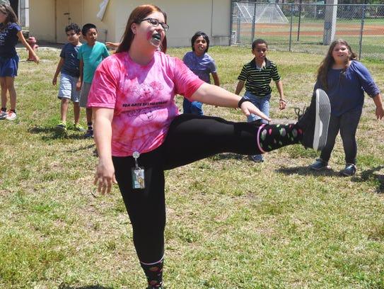 MC3 teacher Jen Damasco leads children in warm up exercises.