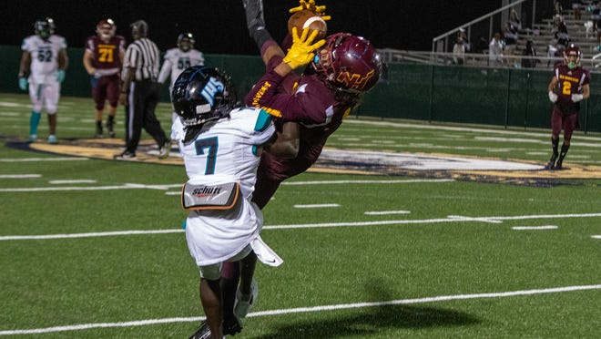 New Hampstead's Kaden Sonnabend (14) comes down with a nice catch while fighting Islands' Terryn Patterson-Bryant (7) for the ball on Friday night at Pooler Stadium.