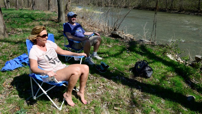 Tammy Williamson and her husband Tony relax by the Sandusky River at the River Cliff Park in Fremont.