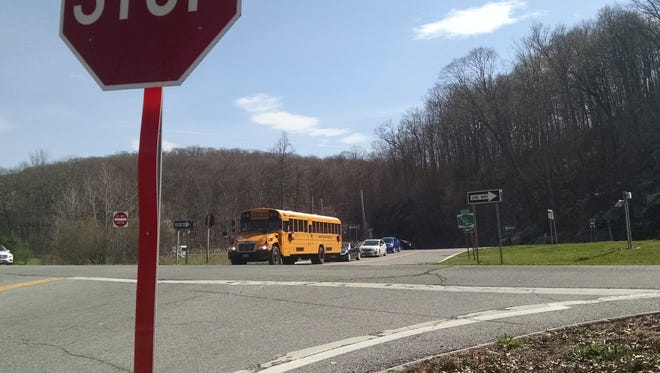 A school bus and several cars wait to cross the Taconic State Parkway on Pudding Street in Putnam Valley.