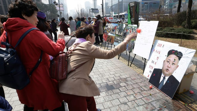A North Korean defector hurls a balloon containing a colored liquid at a portrait of North Korean leader Kim Jong Un during a rally denouncing North Korea's recent threat for war in Seoul on March 30, 2016.