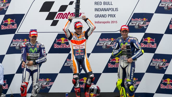 Marc Marquez (93), center, celebrates on the podium with second-place finisher Jorge Lorenzo (99), left, and third-place finisher Valentino Rossi (46) after winning the Indianapolis MotoGP motorcycle race at the Indianapolis Motor Speedway Sunday, Aug. 9, 2015, in Indianapolis.