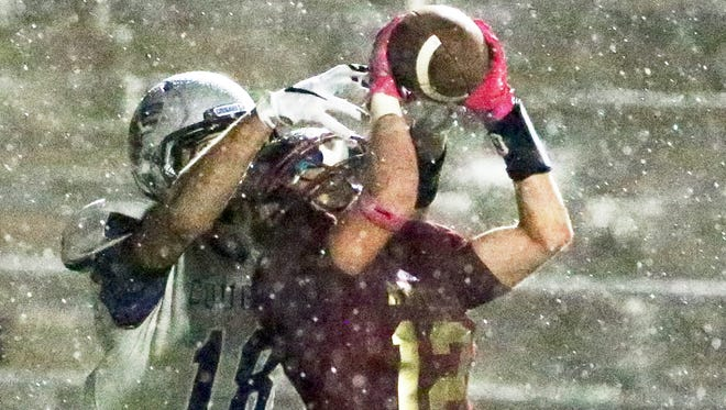 Jorge Hernandez, 12, of El Dorado reaches up to pick off a pass intended for Franklin wide receiver Gunner Romney during a steady rain Friday night at the Socorro Student Activities Complex.