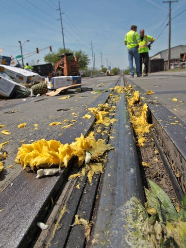 Mashed pineapple pulp lays on the railway tracks at Rural and Massachusetts, after the semi carrying the fruit and stuck on the tracks,  was hit by a train, Tuesday, May 6, 2014.