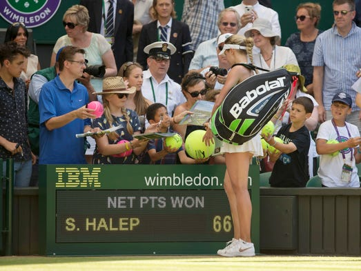 Eugenie Bouchard signs autographs after advancing to the finals of Wimbledon.