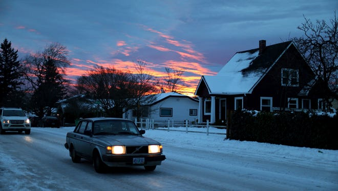 A car maneuvers in icy conditions Tuesday along SE Duke near 72nd Avenue in southeast Portland.