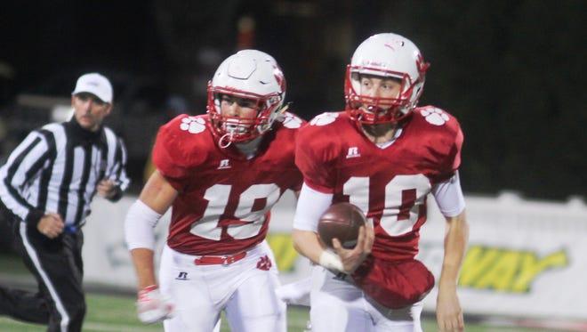 Beechwood quarterback Brayden Burch, 10, runs with Lucas Benson, 19, ready to block.