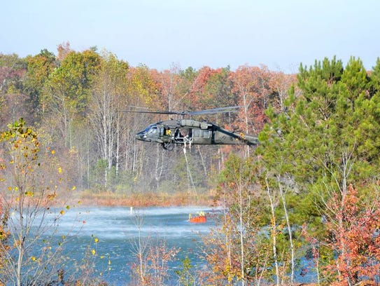 A helicopter scoops water to dump on a brush fire in