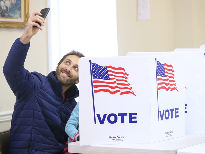 Brian Terzian takes a selfie as he votes with his daughter