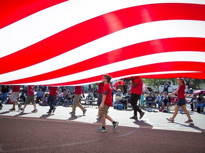 """Marchers carry the """"Hero's Flag"""" during the Veterans"""