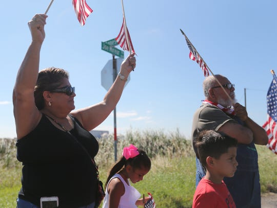 Supporters hold up flags along the highway while waiting
