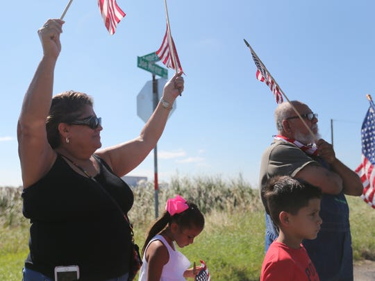 Supporters hold up flags along the highway while waiting for President Trump to pass by Tuesday, Aug. 29, 2017, near Corpus Christi International Airport.