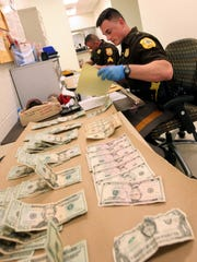 New Castle County Police Department officers log evidence of cash and bags of heroin found in a home in New Castle.