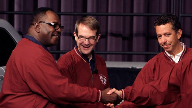 In a July 25, 2011, file photo, from left, General Holiefield, vice president of the United Auto Workers union; UAW President Bob King and Alphons Iacobelli, vice president of employee relations for Chrysler, shake hands