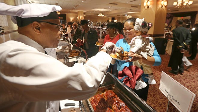 Dr. William Daniels of Rochester serves his Southside Chicago meatloaf to Shauna Clark of Perinton and her 11-month-old daughter, Raina Powe, at the Distinguished Male Cooks event and 25th anniversary celebration on Sunday at the Riverside Convention Center on June 28, 2015.