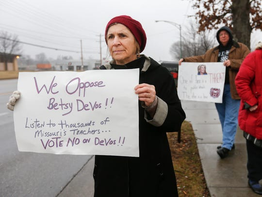 Judith Peavey, of Springfield, holds up a sign while