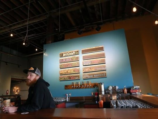 FILE — Jesse Wilson behind the bar when LoveCraft Brewing Company first opened in downtown Bremerton. The brewery is being sold to a new owner.